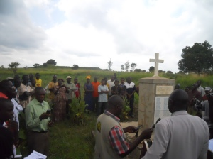 Members of civil society from the DRC and CAR say a prayer alongside people from Lukodi at the memorial for the massacre. June, 2013.